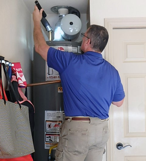 home inspector with flashlight, inspecting water heater