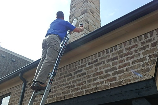 home inspector on ladder, inspecting roof